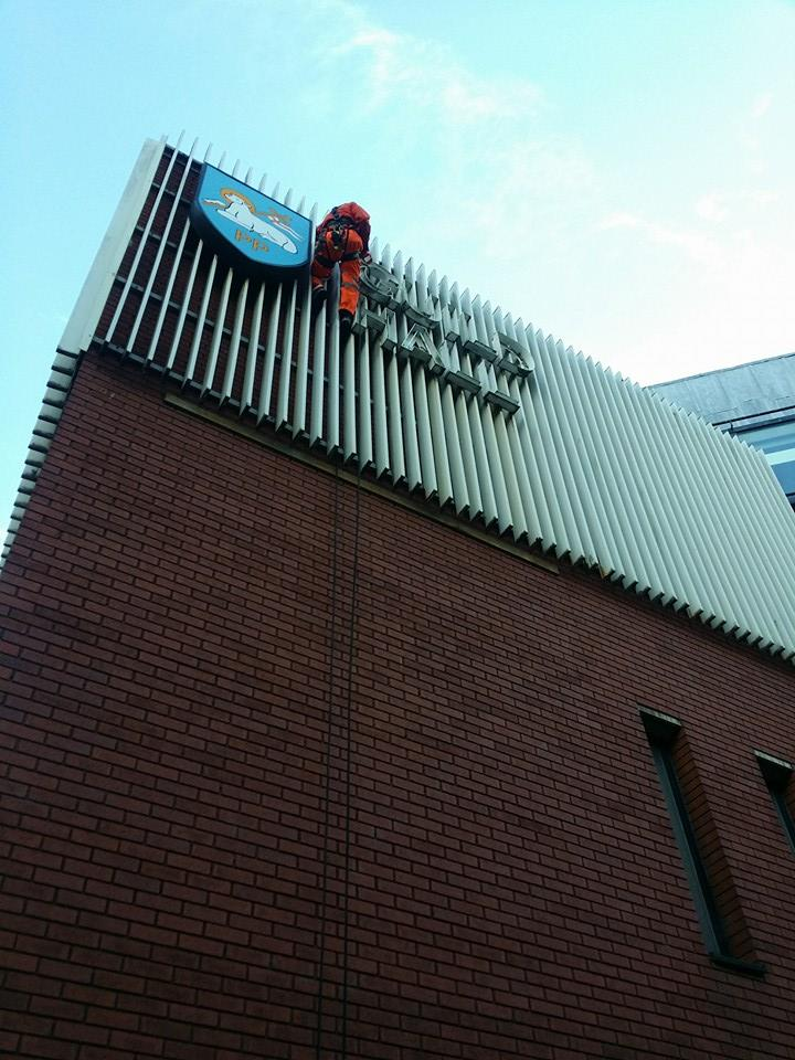 rope access technician decommissions a high level sign at Preston Guild Hall