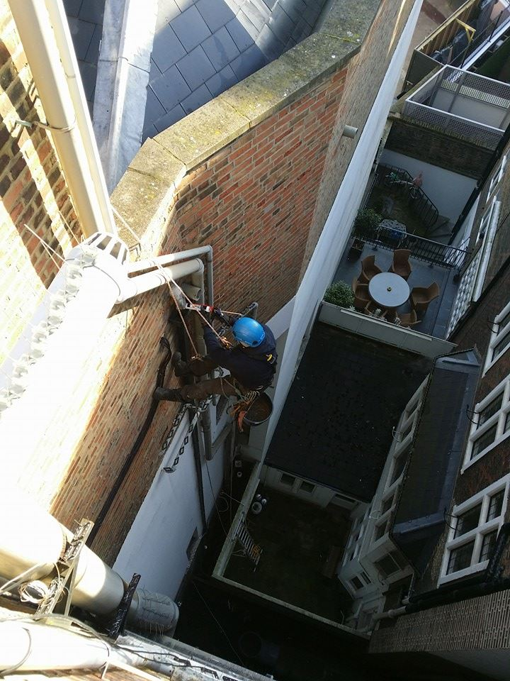 rope access technician repairs guttering at high level.
