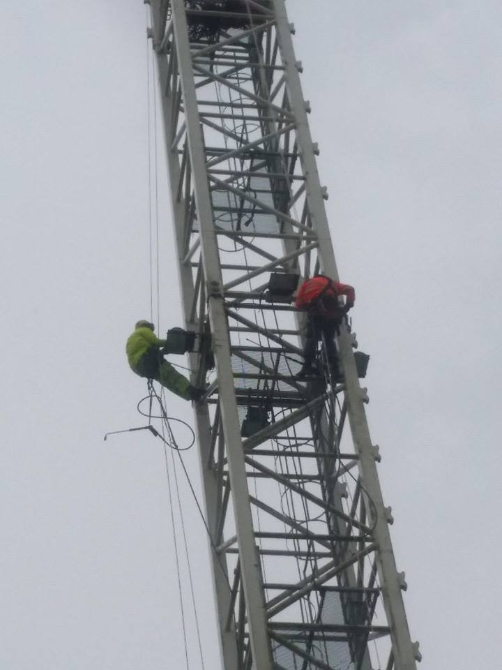 two rope access technicians abseil from a crane to high power pressure wash providing full cleaning service at height