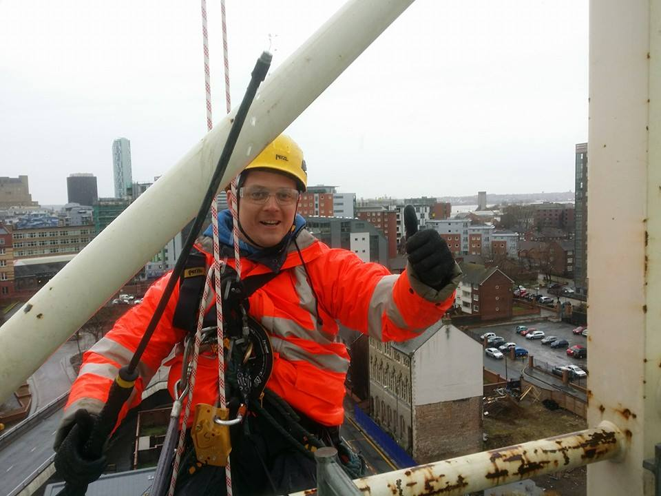 rope access technician dangling on his rope at 50 metres on a tower crane in Liverpool holding his high powered pressure washing lance