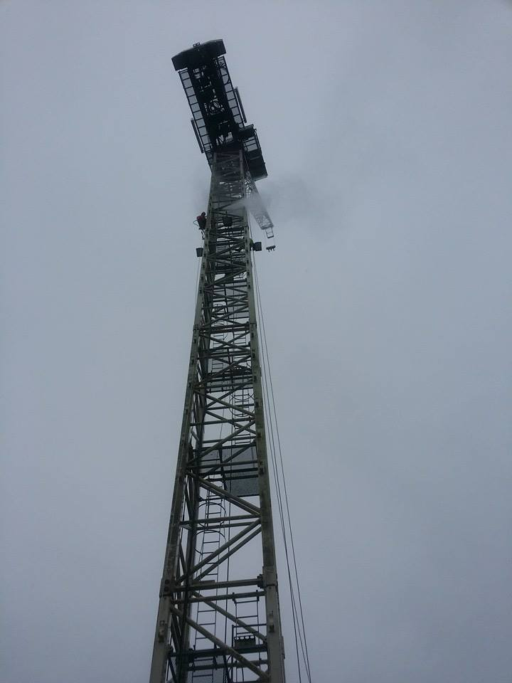 rope access technicians using high temperature low pressure steam to jet wash a 40 metre crane in the centre of Liverpool