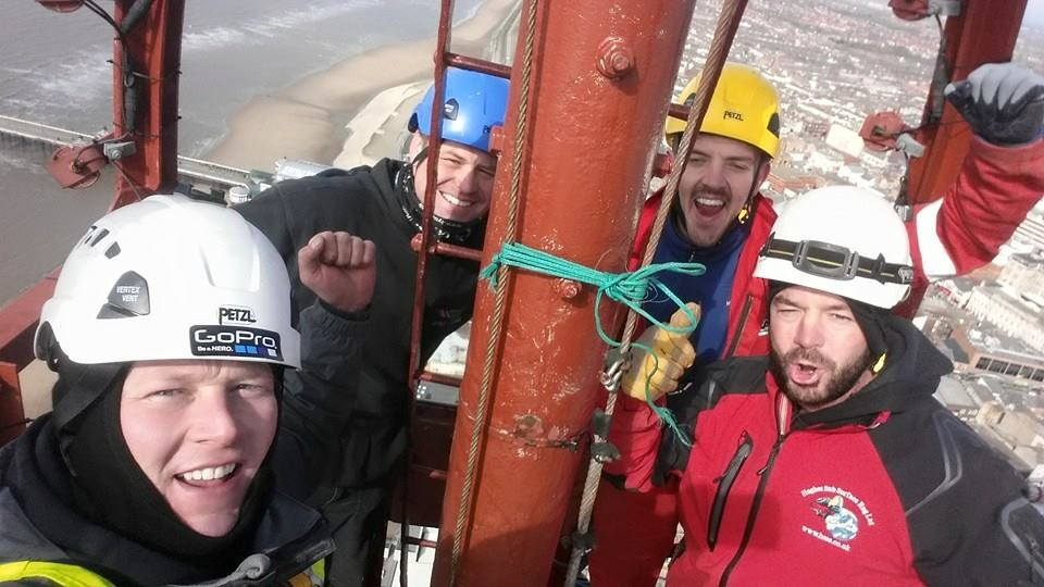 a team of rope access technicians pose for a photo at the top of Blackpool Tower after completing rope access maintenance works