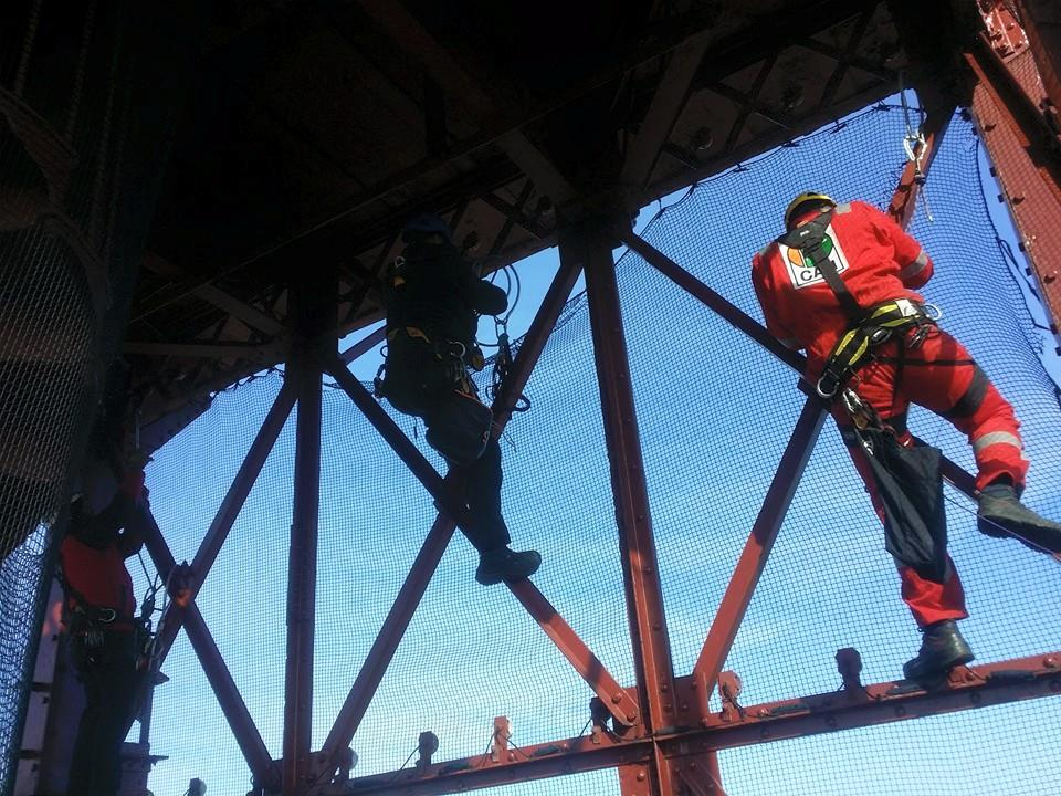 three rope access technicians install safety netting at the top of Blackpool Tower carefully aid climbingon the structure