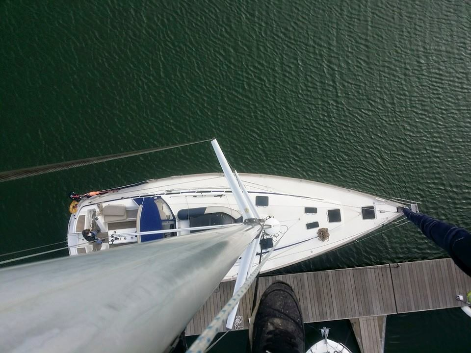a rope access technician takes a picture from the top of a mast at Fleetwood Mariner
