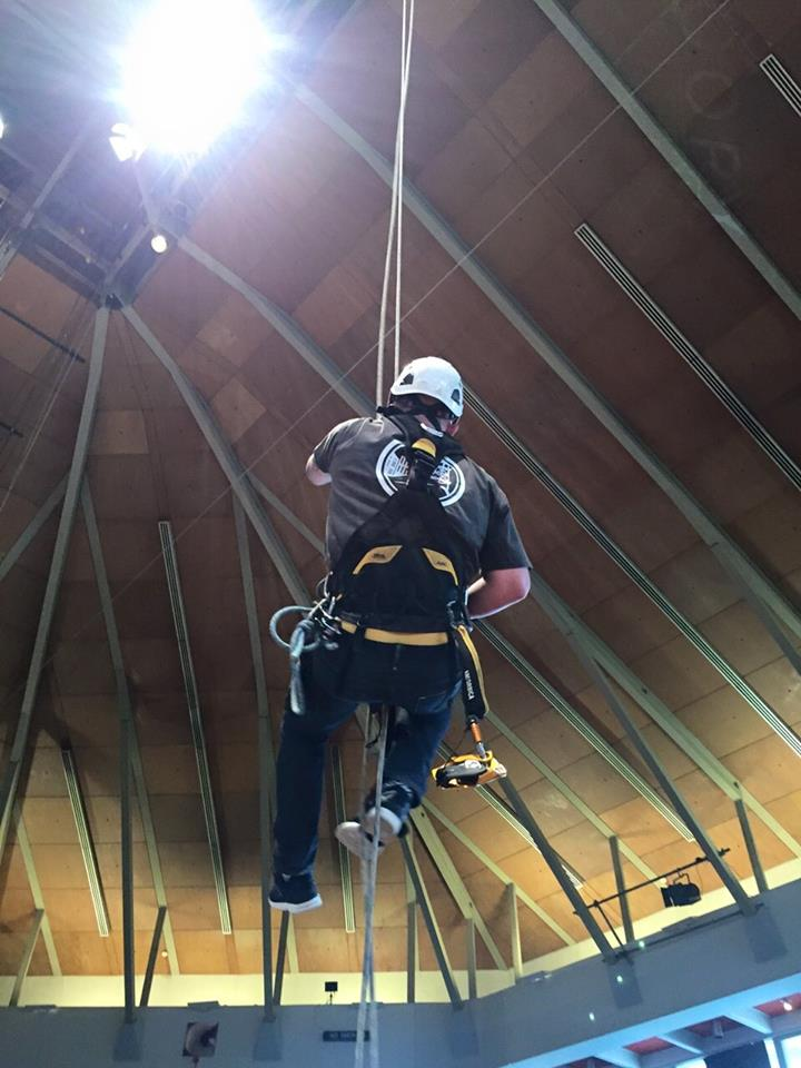 Rope access technician ascends up a rope to change out a light fitting at the Preston Guild Hall Theatre