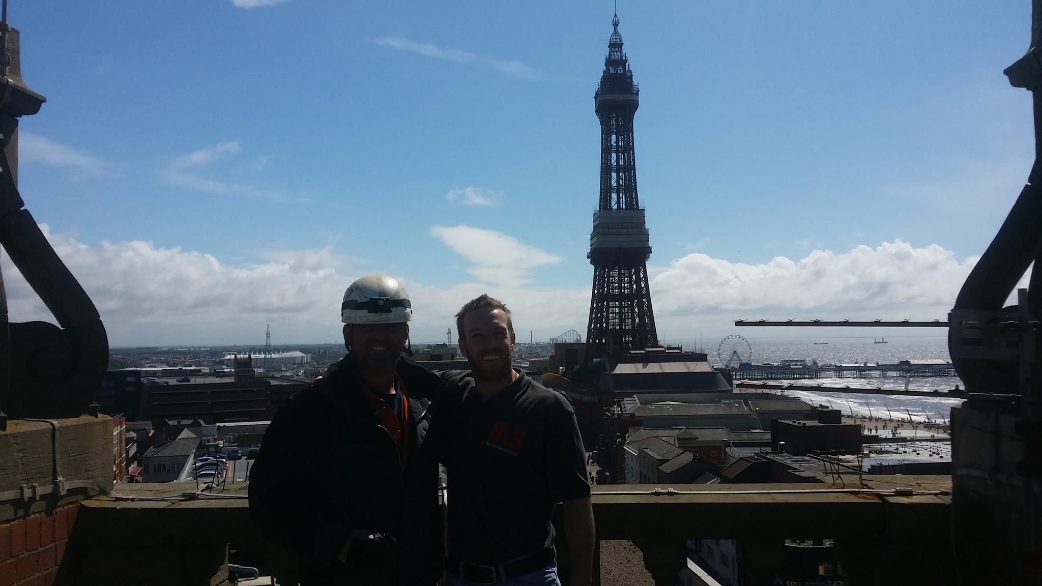 two rope access technicians from High Level Specialists stand on top of Blackpool Council's Town Hall for a photo with Blackpool Tower, Pleasure Beach and the Big Wheel in the background
