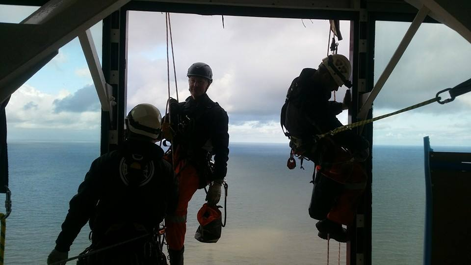 A level 3 technician supervises two rope access technicians carrying out minor repairs