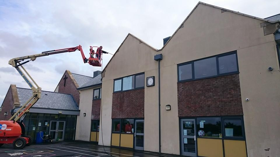 a very large cherry picker is hoisted in the air above a school with the technician caryimg out high level pressure washing