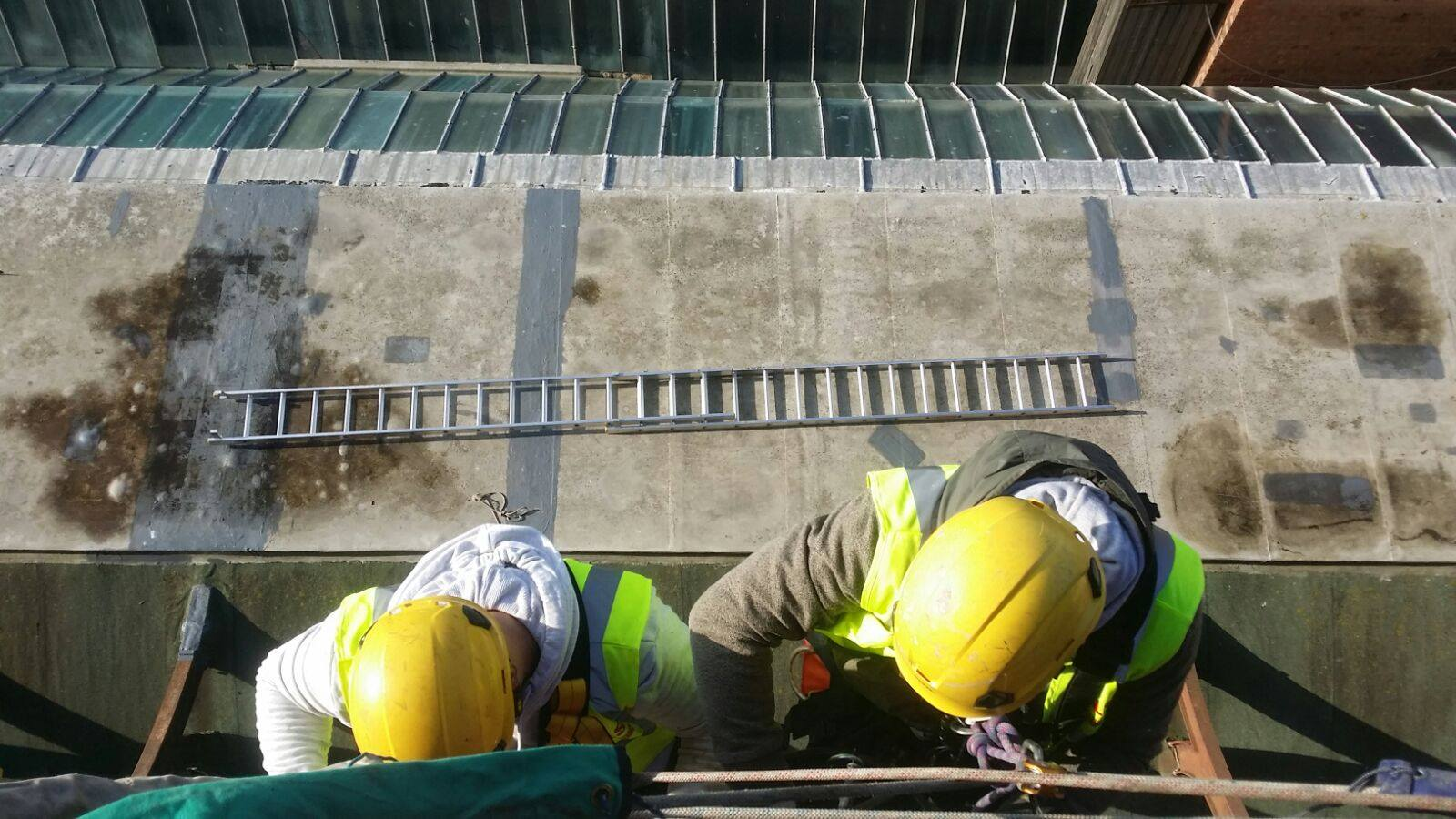 Looking down on two rope access technicians carrying out rope access pointing and high level brick work repair