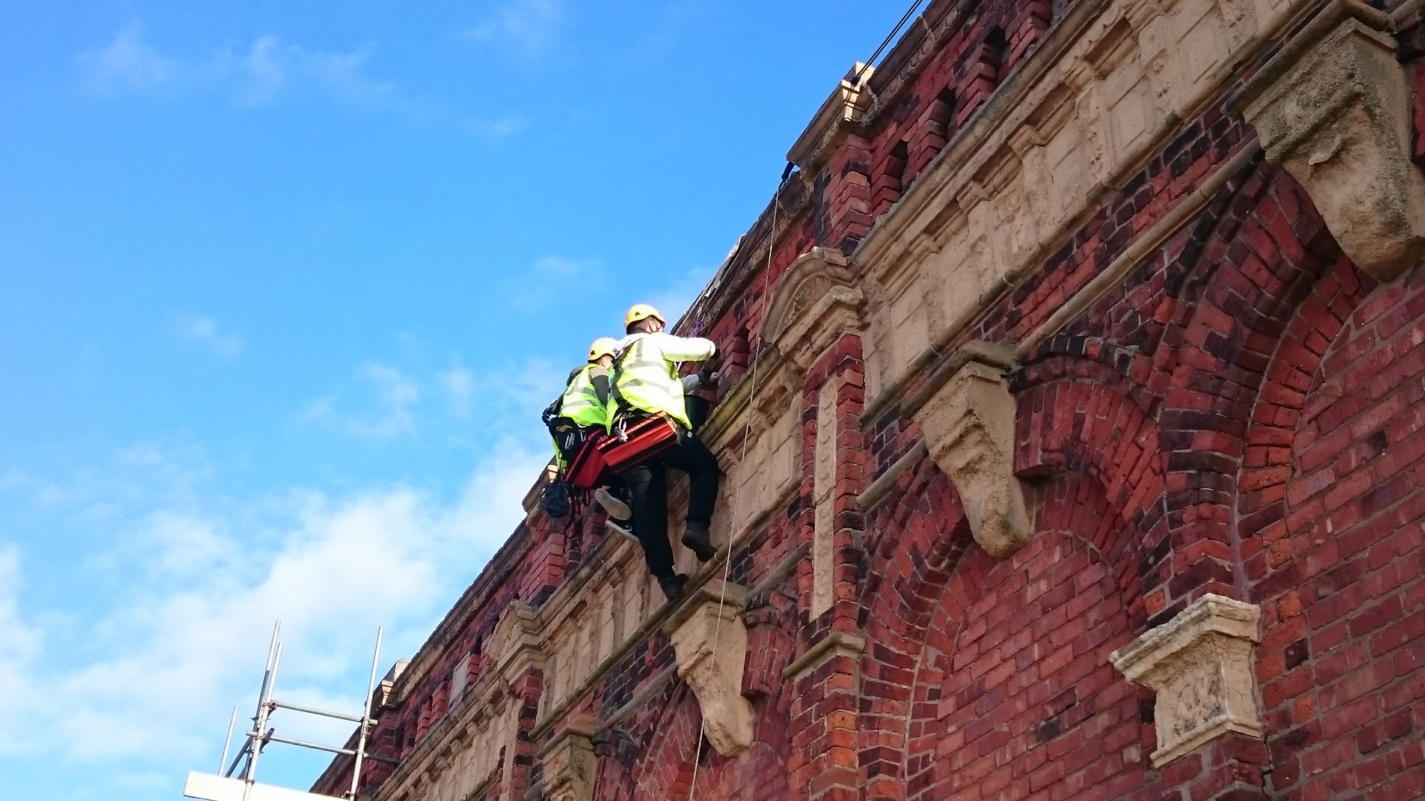 Two rope access technicians working at height on the winter gardens in Blackpool carrying out brickwork repair and pointing works.