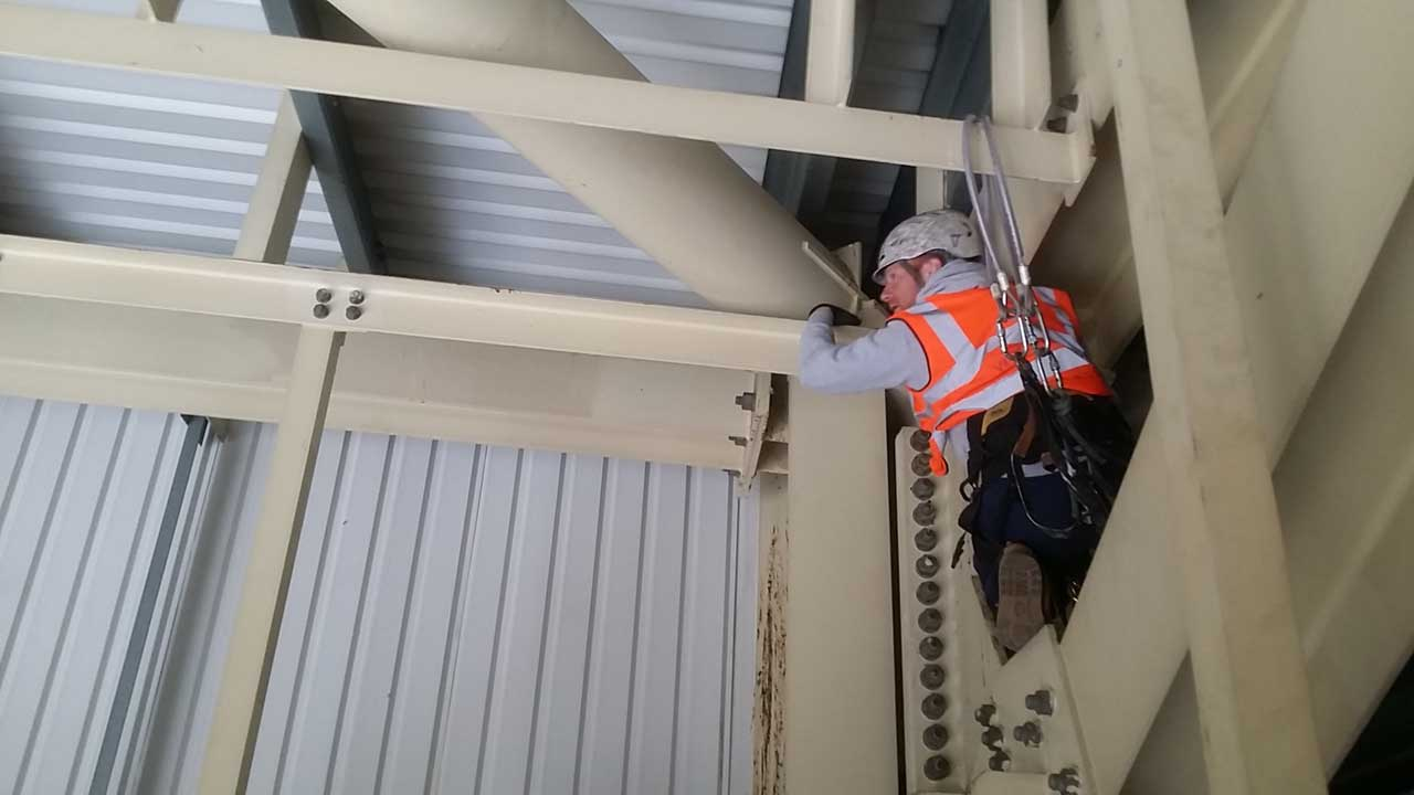 a rope access technician is carefully checking for any bird fouling in the roof space of the Virgin Hanger at Heathrow Airport wearing full hi - viz and full rope access harness carrying out overhead cleaning