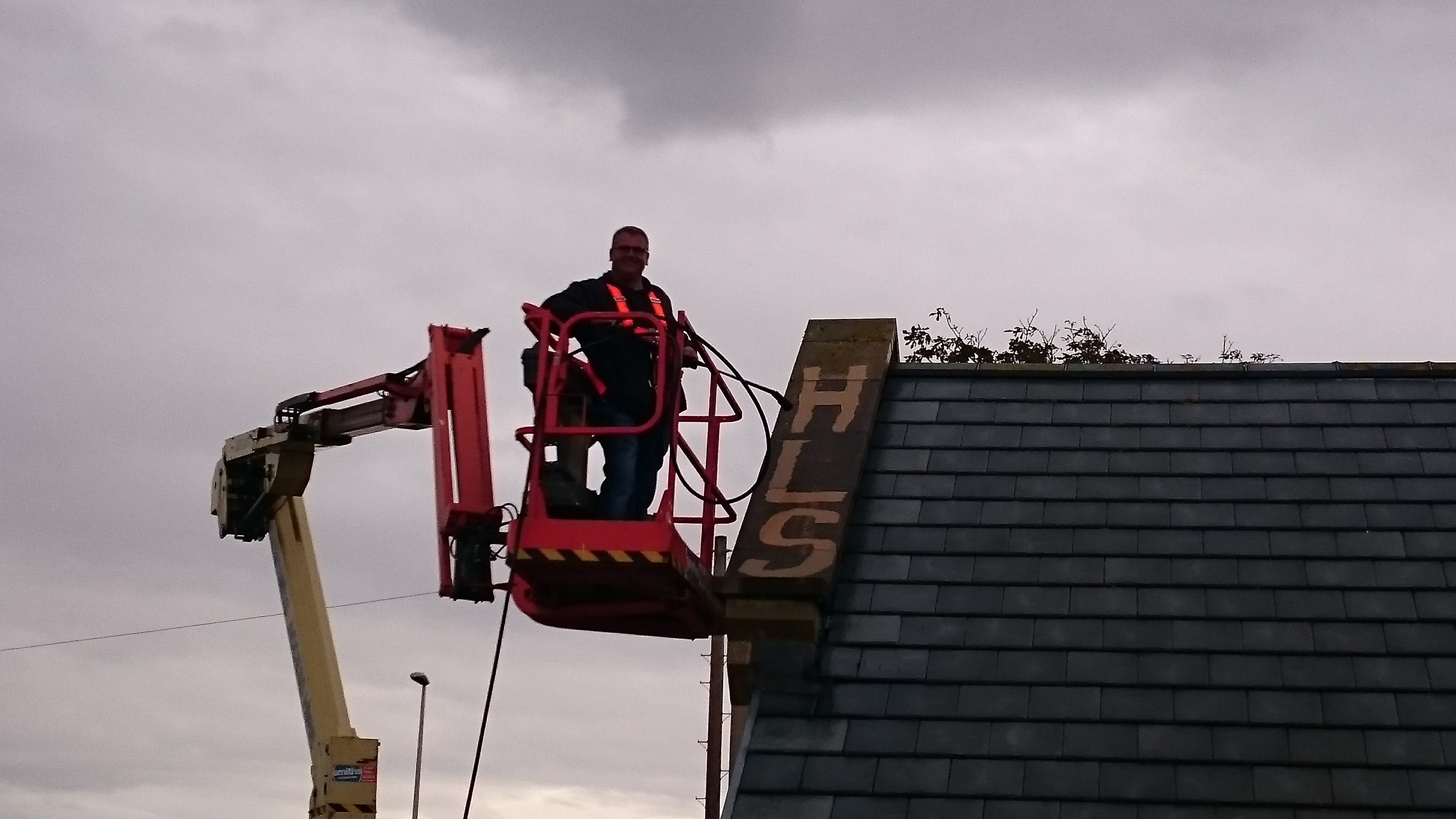 IPAf technician at the top a a cherry picker carrying a pressure washing lance carries out high level cleaning work at a school in Blackpool, Lancashire