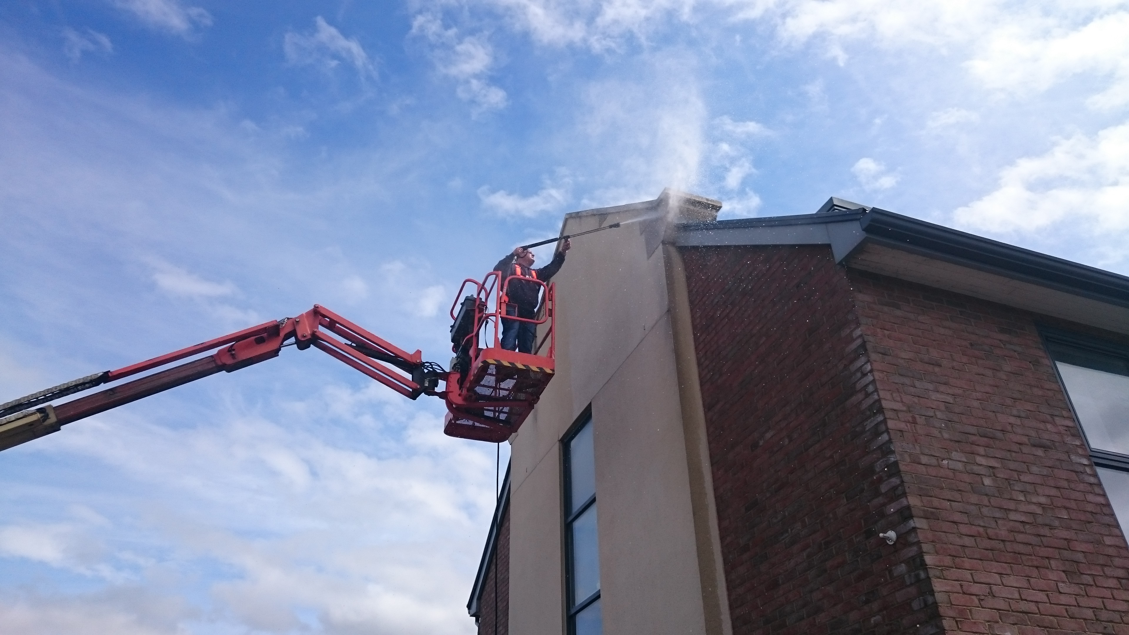 IPAF technician carries out external building cleaning at height using the latest pressure washing technology