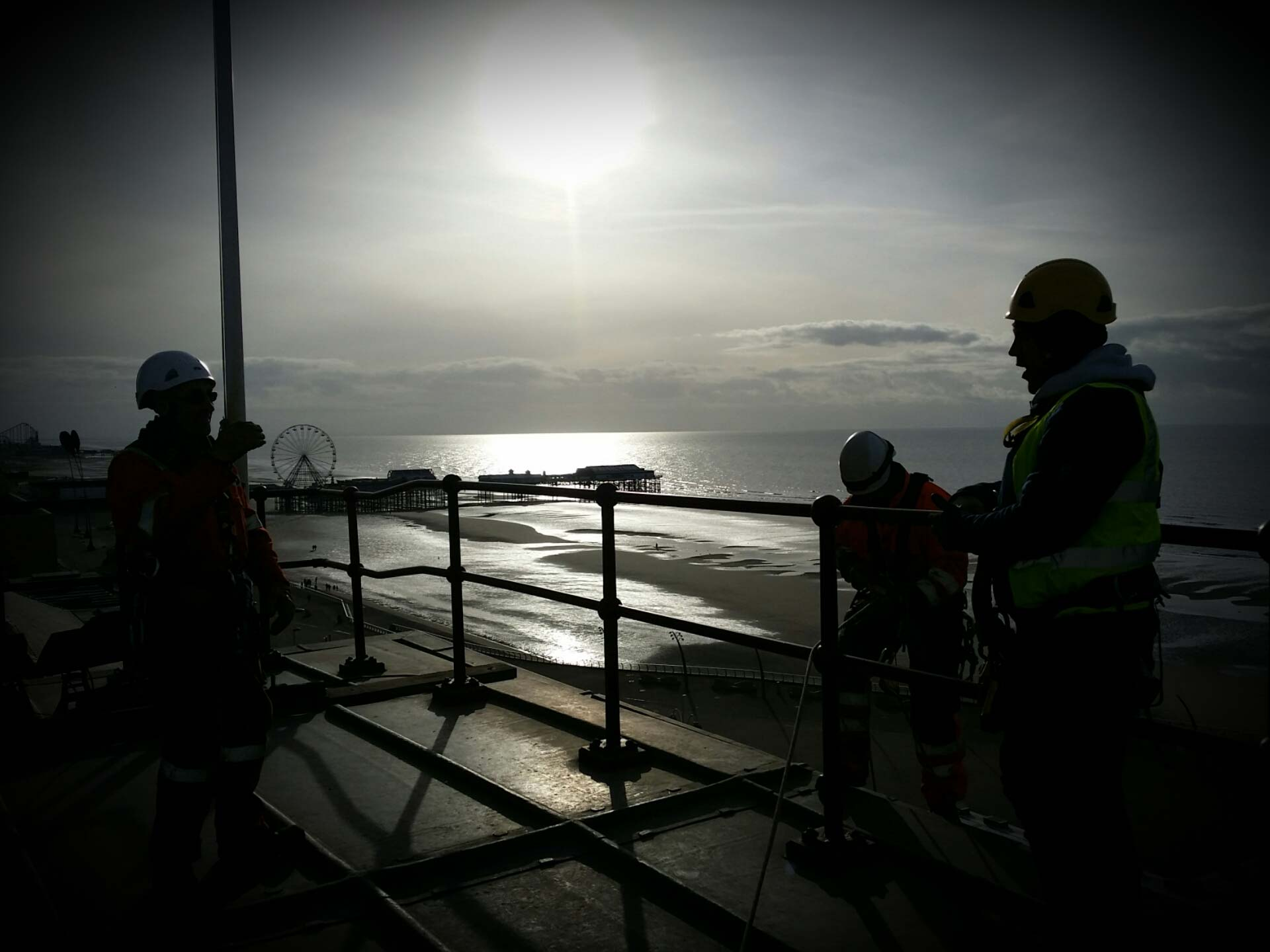 Three rope access technicians are stood on the building at blackpool tower setting up their rope access equipment to carry out rope access works
